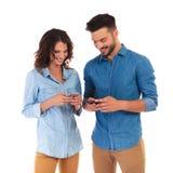 Pares ocasionais felizes que texting em seus telefones imagens de stock royalty free