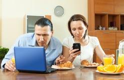 Pares ocasionais felizes usando dispositivos eletrónicos Fotografia de Stock Royalty Free