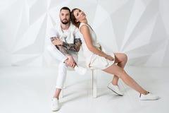 Pares ocasionais perto de uma parede, de um homem e de uma mulher brancos na roupa branca Foto de Stock