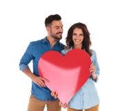 Pares ocasionais que mostram um coração vermelho grande Fotografia de Stock