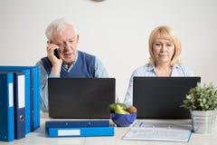 Pares ocupados usando los ordenadores portátiles Foto de archivo libre de regalías