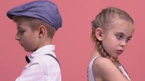 Pares ofendidos de los niños que se colocan de nuevo a uno a, aislado en fondo rosado metrajes