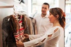 Pares ordinarios que eligen la ropa en el boutique Fotos de archivo libres de regalías