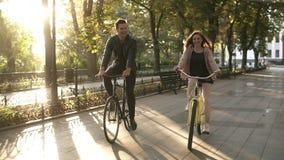 Pares ou amigos novos caucasianos que montam suas bicicletas no parque ou no bulevar vazio da cidade no verão Povos, lazer video estoque