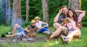 Pares ou famílias que têm o grande tempo que relaxa perto da fogueira Os pares passam o tempo fora no dia ensolarado Fim de seman fotos de stock royalty free