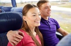 Pares ou passageiros adolescentes felizes no ônibus do curso Foto de Stock
