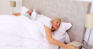 Pares pacíficos que duermen en cama con la mujer que apaga la alarma almacen de metraje de vídeo