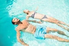 Pares pacíficos que flotan en la piscina Imágenes de archivo libres de regalías