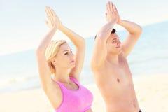 Pares pacíficos que meditan en la playa Imagen de archivo libre de regalías