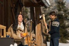 Pares pela casa de campo do inverno da neve que aprecia o chá Imagem de Stock