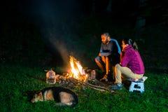 Pares pelo fogo do acampamento na noite Fotos de Stock