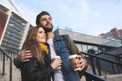 pares pensativos no amor com o café para ir olhar afastado Foto de Stock Royalty Free