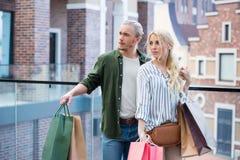 Pares pensativos que estão com os sacos de compras nas mãos na alameda Foto de Stock Royalty Free
