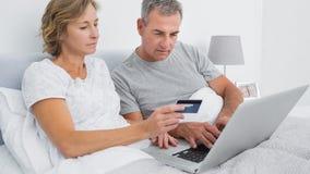 Pares pensativos usando seu portátil para comprar em linha Fotografia de Stock Royalty Free