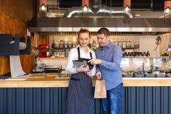 Pares pequenos do proprietário empresarial em pouco restaurante da família que olha a tabuleta para ordens em linha imagem de stock