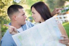 Pares perdidos e confusos da raça misturada que olham sobre o mapa fora Imagem de Stock