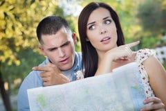 Pares perdidos e confusos da raça misturada que olham sobre o mapa fora Fotos de Stock