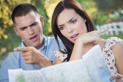 Pares perdidos y confusos de la raza mixta que miran sobre mapa afuera Fotos de archivo
