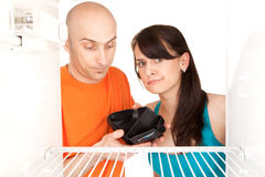 Pares pobres que miran en refrigerador Imagen de archivo libre de regalías