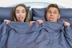 Pares positivos adultos en cama bajo cubiertas que muestran la lengua y que miran la cámara fotos de archivo libres de regalías