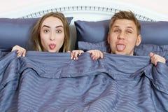 Pares positivos adultos en cama bajo cubiertas que muestran la lengua y que miran la c?mara imágenes de archivo libres de regalías