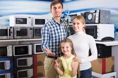 Pares positivos com a criança na loja com eletrônica imagem de stock