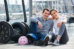 Pares positivos de los turistas que se relajan cerca de segways Foto de archivo libre de regalías