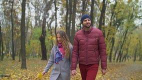 Pares positivos en el amor que disfruta de la naturaleza en parque del otoño almacen de metraje de vídeo