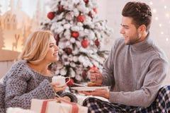 Pares positivos felizes que comem o café da manhã Imagens de Stock Royalty Free