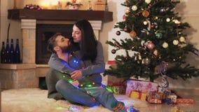 Pares positivos jovenes que se sientan en el árbol de navidad en el piso en el cuarto Concepto del tiempo del A?o Nuevo y de la N almacen de metraje de vídeo
