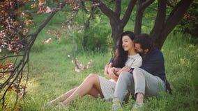 Pares preciosos jovenes en aire libre floreciente del parque de la primavera metrajes