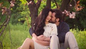 Pares preciosos jovenes en aire libre floreciente del parque de la primavera almacen de video