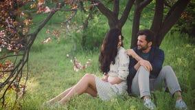 Pares preciosos jovenes en aire libre floreciente del parque de la primavera almacen de metraje de vídeo