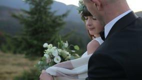 Pares preciosos junto en la montaña El novio cubre a la novia con una cubierta Cámara lenta almacen de video
