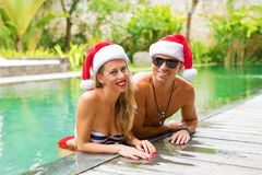 Pares preciosos que llevan los sombreros de Papá Noel por la piscina Imagen de archivo