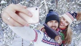 Pares preciosos sonrientes que toman el selfie en madera sitiada por la nieve metrajes