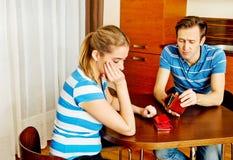 Pares preocupantes que se sientan en la tabla con las carteras vacías fotografía de archivo libre de regalías