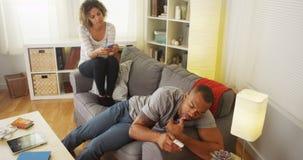 Pares pretos confundidos por smartphones Foto de Stock Royalty Free