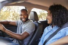 Pares pretos novos em um carro que olha se que sorri imagens de stock royalty free