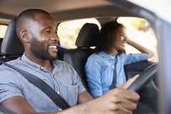 Pares pretos novos no carro em um sorriso anticipar da viagem por estrada fotografia de stock