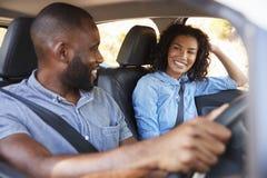 Pares pretos novos no carro na viagem por estrada que sorri em se foto de stock