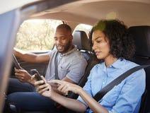 Pares pretos novos que navegam com smartphone em uma viagem por estrada imagens de stock royalty free