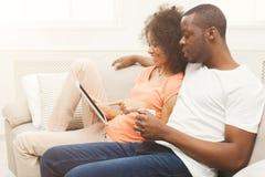 Pares pretos que fazem usando a tabuleta digital em casa fotografia de stock royalty free