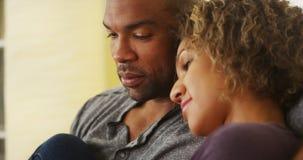 Pares pretos que sentam-se no sorriso do sofá imagem de stock