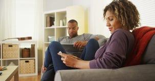 Pares pretos usando dispositivos eletrónicos no sofá imagem de stock royalty free