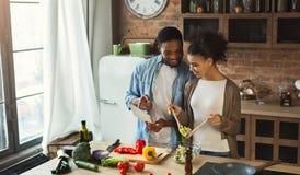 Pares pretos usando a tabuleta digital ao preparar o jantar fotos de stock