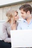 Pares profesionales jovenes usando la computadora portátil Imagen de archivo libre de regalías