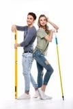 Pares profissionais novos que guardam o rolo de pintura e que constroem isolado ao nível no branco Foto de Stock