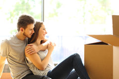Pares que abraçam casa nova movente imagem de stock