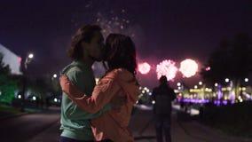 Pares que abraçam e que beijam contra fogos-de-artifício